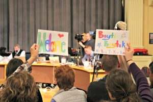 Supporters of a resolution to welcome Syrian refugees in Burlington hold handmade signs during a city council meeting on Monday, Nov. 28.