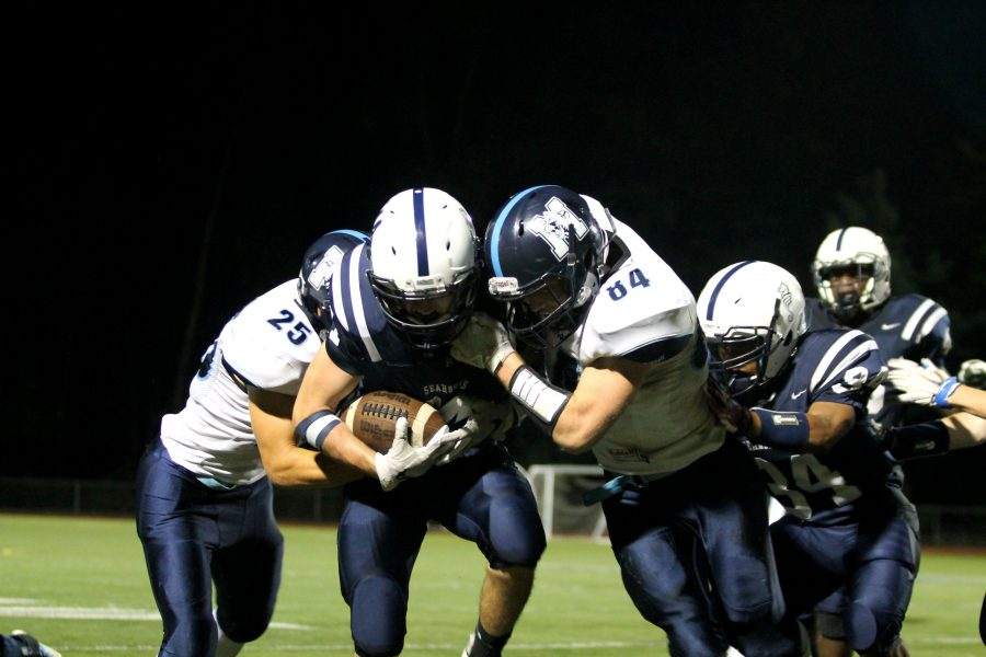 BHS ball carrier is tackled by two MMU defenders
