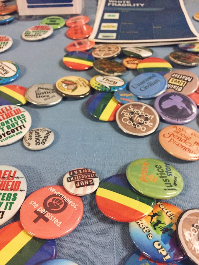 One of many informative tables set up in the A building hallway during the Symposium held a variety of social justice themed pins.