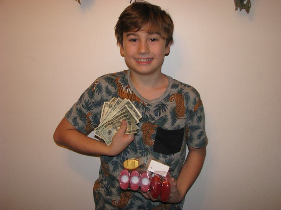 Logan Morey, 13, poses with donations for the Back at-it Packs. Photo: Courtesy of Shannon Morey